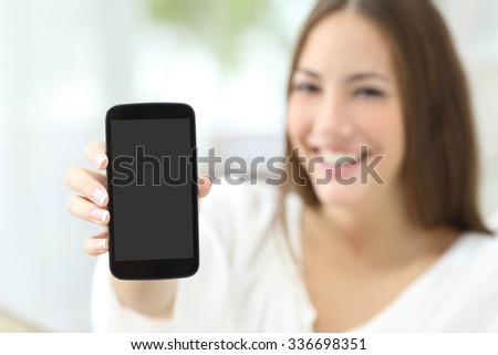 Happy housewife showing a blank smart phone screen at home - stock photo