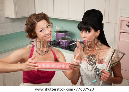 Happy housewife shows her smoking friend a dish in the kitchen - stock photo