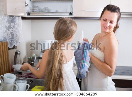 Happy housewife with daughter washing plates at home