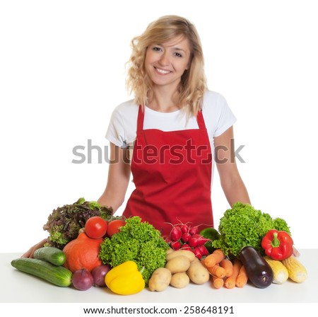 Happy housewife with red apron and fresh vegetables - stock photo