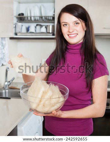 Happy housewife with rice noodles in home kitchen
