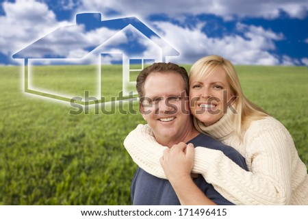 Happy Hugging Couple in Grass Field with Ghosted House Figure Behind Them. - stock photo