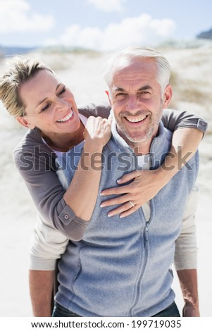 Happy hugging couple on the beach looking at camera on a bright but cool day - stock photo