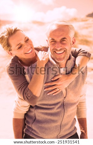 Happy hugging couple on the beach looking at camera on a bright but cool day