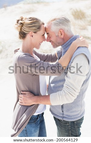 Happy hugging couple on the beach looking at each other on a bright but cool day - stock photo