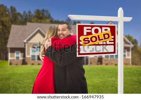 Happy Hugging Mixed Race Couple in Front of Their New House and Sold Real Estate Sign.