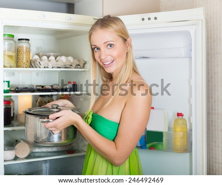 Happy hungry girl with pan near fridge  at her home - stock photo