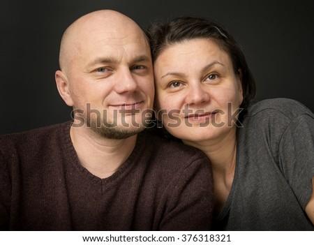 Happy husband and his wife, studio portrait - stock photo