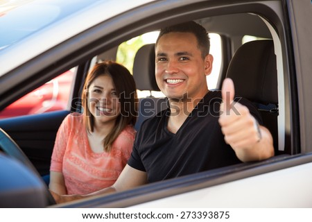 Happy husband and wife enjoying a car ride and giving a thumb up because they really like it - stock photo