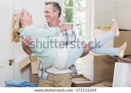 Happy husband carrying his wife in their new house - stock photo