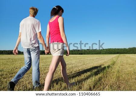 Happy husband, wife hold walk in field near wood, side - stock photo