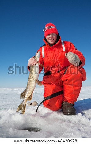 Happy ice fisherman holding a northern pike