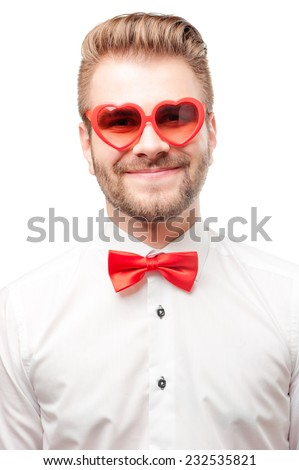 Happy in love. Young handsome smiling man isolated on white background wearing heart shaped sunglasses and red bow tie. - stock photo