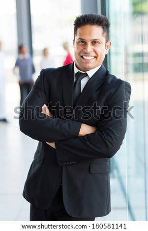happy indian business man standing in office - stock photo