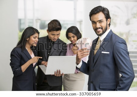 Happy Indian businessman standing holding Indian rupees with his colleagues at office - stock photo