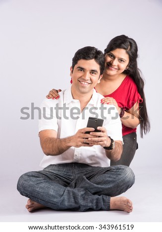 Happy indian couple holding smartphone in christmas time, asian couple and smart phone, isolated on white background, front view