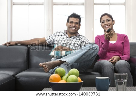 Happy Indian couple on the sofa watching tv in the living room - stock photo