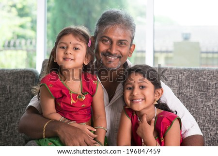 Happy Indian family at home. Asian father and daughters sitting on sofa smiling. Parent and children indoor lifestyle. - stock photo