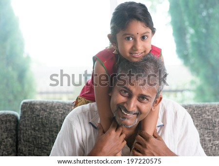 Happy Indian family at home. Asian father piggyback her daughter, sitting on sofa. Parent and child indoor lifestyle. - stock photo