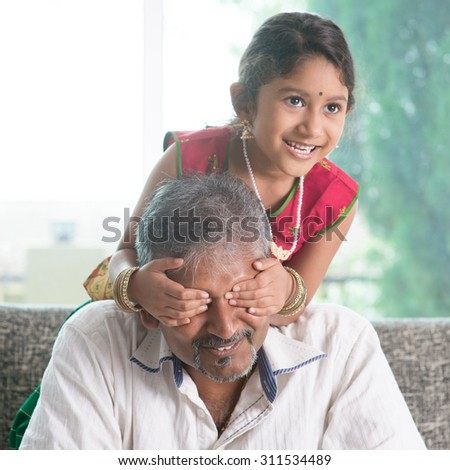 Happy Indian family at home. Asian girl surprising her father by covering dad eyes. Parent and child indoor lifestyle. - stock photo