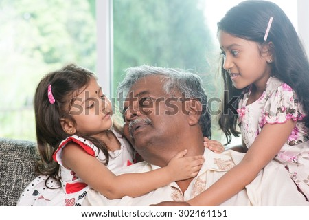 Happy Indian family at home. Asian grandfather and granddaughters having sweet conversation. Grandparent and grandchildren indoor lifestyle. - stock photo