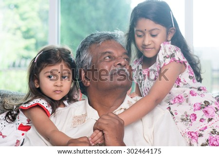 Happy Indian family at home. Asian grandfather and granddaughters playing together. Grandparent and grandchildren indoor lifestyle. - stock photo