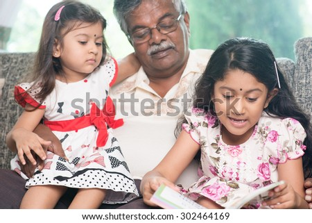 Happy Indian family at home. Asian grandfather and granddaughters reading story book. Grandparent and grandchildren indoor lifestyle. - stock photo