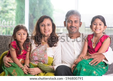Happy Indian family at home. Asian parents and children living lifestyle, sitting on couch indoor happily. - stock photo