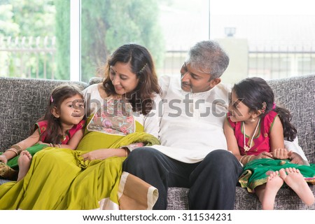 Happy Indian family at home. Asian parents bonding with their children, sitting on sofa. Adults and kids indoor lifestyle.