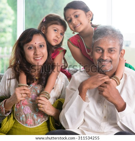 Happy Indian family at home. Asian parents piggyback their children. Adults and kids indoor lifestyle. - stock photo