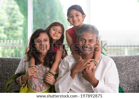Happy Indian family at home. Asian parents piggyback their kids, sitting on sofa. Parents and children indoor lifestyle.