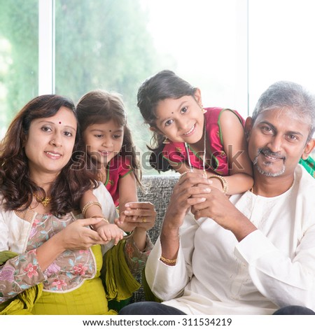 Happy Indian family at home. Asian parents with their kids, sitting on sofa. Parents and children indoor lifestyle. - stock photo