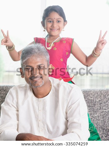 Happy Indian family at home. Focus on father. Adults and kids indoor lifestyle. - stock photo