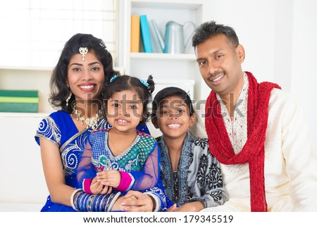 Happy Indian family at home. Living lifestyle of parents and children in their traditional dress in modern house. - stock photo