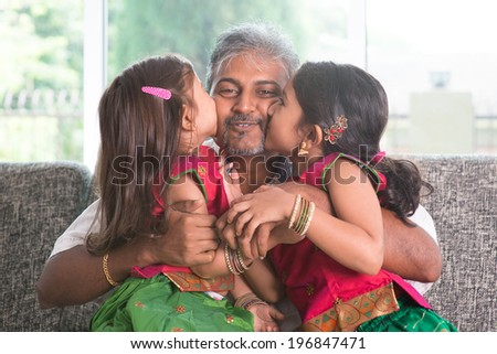 Happy Indian family at home. Two cute Asian girls kissing father, sitting on sofa. Parent and children indoor lifestyle. - stock photo