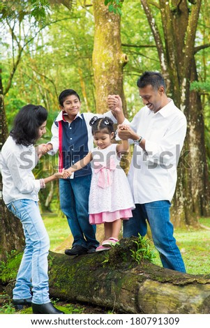 Happy Indian family at outdoor. Candid portrait of parents and children having fun at garden park. Exploring nature, leisure lifestyle. - stock photo