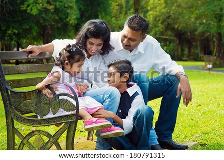 Happy Indian family at outdoor park. Candid portrait of parents and children having fun at garden park. - stock photo