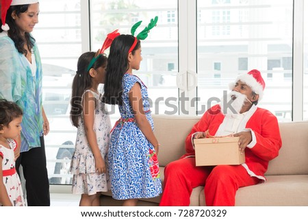 Happy Indian family celebrating Christmas holidays, with gift box and santa at home, Asian people festival mood indoors.