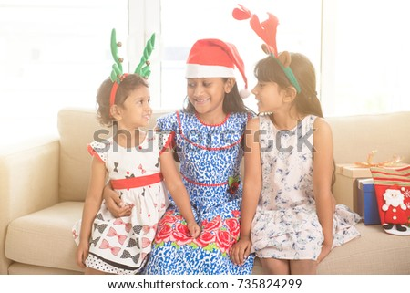 Happy Indian family celebrating Christmas holidays, with gift box and santa hat sitting on sofa at home, adorable Asian children on festival mood.