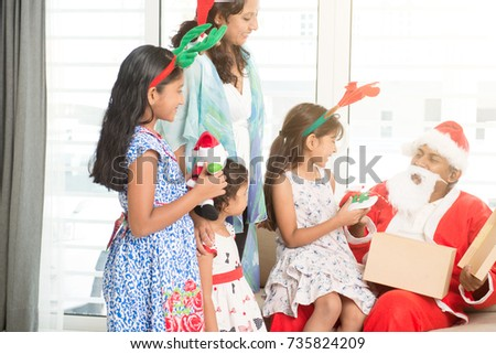 Happy Indian family celebrating Christmas holidays, with gift box and santa hat sitting on sofa or couch at home, Asian parents and children festival mood indoors.