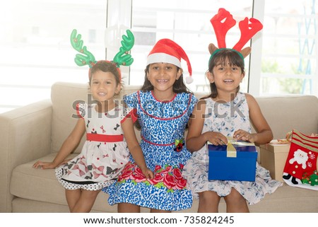 Happy Indian family celebrating Christmas holidays, with gift box and santa hat sitting on sofa or couch at home, Asian children on festival mood.