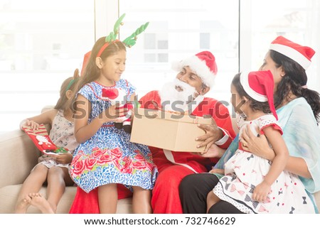 Happy Indian family celebrating Christmas holidays, with gift box and santa sitting on sofa or couch at home, Asian people festival mood indoors.