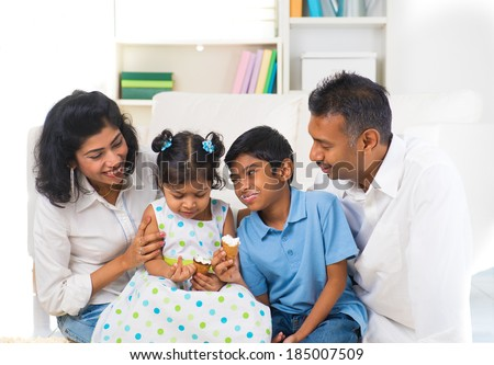 happy indian family enjoying eating ice cream indoor - stock photo