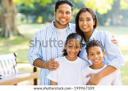 happy indian family standing at the park - stock photo