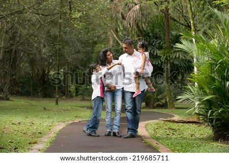 happy indian family walking outdoor in the park - stock photo