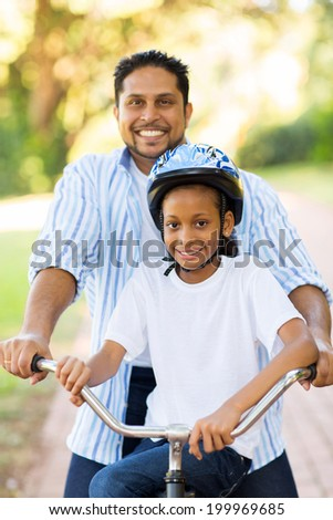 happy indian father and daughter outdoors on a bike - stock photo