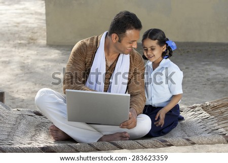 Happy Indian father and daughter using laptop - stock photo