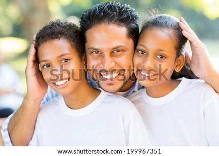 happy indian father and kids closeup portrait outdoors - stock photo