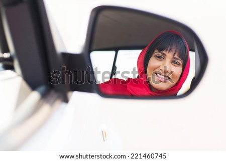 happy indian female driver looking at side mirror - stock photo