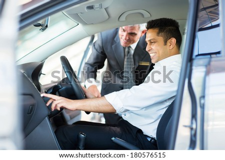 happy indian man checking car features at showroom - stock photo